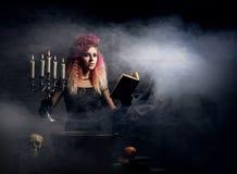 Bruja joven y hermosa que hace brujería en la mazmorra Foto de archivo