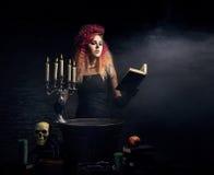 Bruja joven y hermosa que hace brujería en la mazmorra Imágenes de archivo libres de regalías