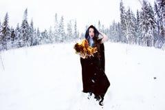 Bruja o mujer en capa negra con la bola de fuego en el bosque blanco de la nieve Fotos de archivo