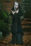 Bruja oscura que presenta en el bosque Imagenes de archivo