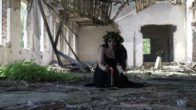 Bruja que conjura y que invoca bebidas espirituosas maléficas con el ensalmo y velas en una mansión arruinada abandonada almacen de metraje de vídeo