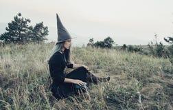 Bruja que se sienta en campo Foto de archivo libre de regalías