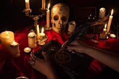 Bruja que sostiene un libro con pentagram, el cráneo y las velas Imagen de archivo