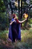 Bruja que sostiene una bola de fuego imagenes de archivo