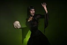 Bruja sensual que sostiene un cráneo en su mano Foto de archivo libre de regalías