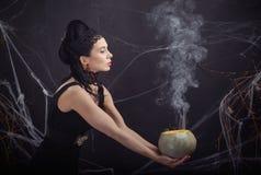 Bruja traviesa del traje de Halloween y su poción mágica Imágenes de archivo libres de regalías