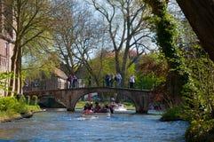 Brujas, Bélgica - 10 de abril: Los turistas no identificados visitan la ciudad medieval de Brujas usando los barcos típicos sobre  Fotos de archivo