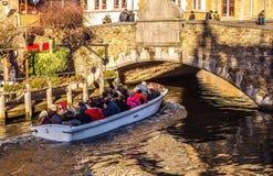 BRUJAS, BÉLGICA - 17 DE ENERO DE 2016: Transporte el barco con los turistas que miran en el edificio antiguo de la ciudad medieva Imagen de archivo libre de regalías