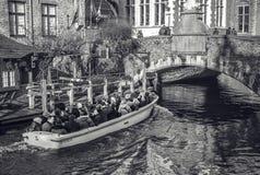 BRUJAS, BÉLGICA - 17 DE ENERO DE 2016: Transporte el barco con los turistas que miran en el edificio antiguo de la ciudad medieva Fotografía de archivo