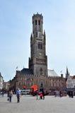 Brujas, Bélgica - 11 de mayo de 2015: Campanario turístico de la visita de Brujas en el cuadrado de Grote Markt Imágenes de archivo libres de regalías