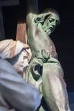 Brujas - estatua de Maria santa debajo de Cristo en la cruz de poco parque cerca de Sint Janshospital Imágenes de archivo libres de regalías