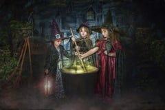 Brujas jovenes que revuelven la caldera foto de archivo