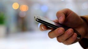 Bruk för en hand för man` s svärtar smartphonen på bakgrunden som går folk och bokehljus stock video
