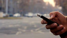Bruk för en hand för man` s svärtar smartphonen på bakgrundscityscapen med bilar arkivfilmer