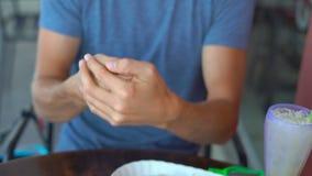 Bruk för ung man en handsanitizer i ett kafé lager videofilmer