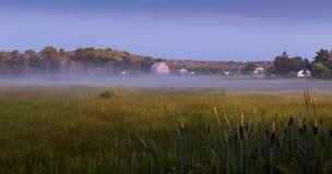 Bruka med en wood ladugård och hus bredvid ett gräsfält på soluppgång royaltyfri bild