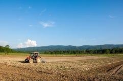 Bruka med traktoren och plogen i fält med berget Papuk i th Royaltyfri Foto