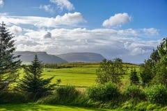 Bruka område som omges av solsken i en dal med berg fotografering för bildbyråer