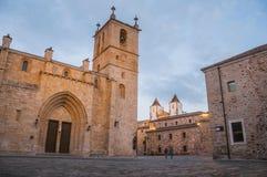 Brukowa kwadrat z kościół, budynkami i ludźmi przy półmrokiem w Caceres gothic, zdjęcie royalty free