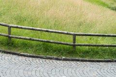 Brukowiec droga z drewnianym ogrodzeniem i wysoką wildflower łąką fotografia stock