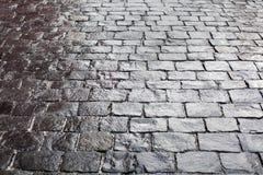 Brukowowie na bruku tle, kamiennych chodniczek tekstury szarość lub czerń kolorze, mokrego cegły drogowej powierzchni wzoru odgór zdjęcia stock