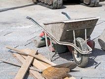 Brukowy pracy wheelbarrow wiadro i miotła Obraz Royalty Free