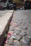 Brukująca ulica w Rzym, Włochy z papierowymi streamers w rynnie obraz stock