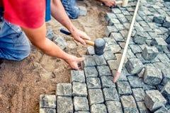 brukujący z granitowymi kamieniami, pracownikami używa przemysłowych brukowów dla brukować taras, drogą lub chodniczkiem, Obraz Stock