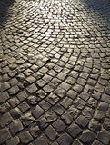 Brukuje kamiennego ulicznego tło przy zmierzchem Fotografia Stock