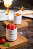 Brulee, gebrande room van de room diende brulee room met aardbeien op houten raad op de restaurantlijst Gastronomisch Dessert exe stock foto