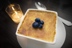 Brulee guld- kräm, fyra blåbär, bot som äter middag efterrätten, stearinljus, sked, mörk wood tabell royaltyfri foto