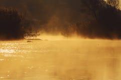 Brume d'or au-dessus de l'eau au lever de soleil Photographie stock