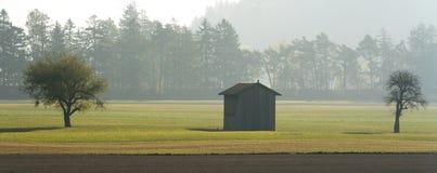 Brume de matin dans une vallée de montagne avec des champs et une vieille grange en bois et arbres avec la forêt en brouillard de photos libres de droits