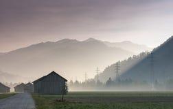 Brume de matin dans une vallée de montagne avec des champs et de vieilles granges en bois et treillager les lignes électriques et image libre de droits