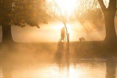 Brume et brouillard de début de la matinée au-dessus de lac avec des passants par Image libre de droits