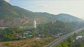 Brummen-Ansätze über Straße zu Buddha-Statue vom Dorf stock video