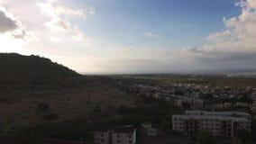 Brummen, das über die Belle Etoile-Stadt in Mauritius, nah an Port Louis fliegt Stürmischer Himmel und Berg im Hintergrund stock video