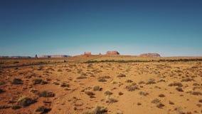 Brummen, das niedrig über trockene amerikanische Sandsteinwüste nahe Monument-Tal in Arizona und in Utah, sonniger blauer Himmel  stock video footage