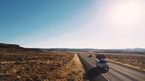 Brummen, das niedrig über typische amerikanische Wüstenlandstraßen-Landschaftsstraße mit den Autos vorbei überschreiten und ersta stock footage
