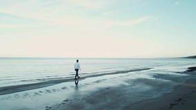 Brummen eines Mannes, der entlang den Strand im Sommer, folgend geht stock video footage