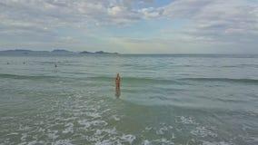 Brummen entfernt vom Mädchen, das vom Ozean gegen Wellenbrandung herausgeht stock video