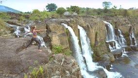 Brummen entfernt von ändernder Yogahaltung des Mädchens durch Wasserfall stock footage