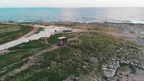 Brummen fliegt durch schmale touristische Fußgängerpromenade mit den Leuten, die auf felsigem Strand mit Ozean am Horizont sich e stock video footage