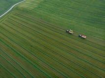 Brummen geschossen vom landwirtschaftlichen Feld mit den Traktoren, die Heu ernten lizenzfreie stockbilder