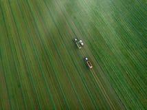 Brummen geschossen vom landwirtschaftlichen Feld mit den Traktoren, die Heu ernten lizenzfreie stockfotos