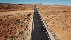 Brummen nach silbernem Auto auf leerer Wüstenlandstraßenstraße in Arizona, Kameraneigungen decken bis flache Landschaft und Skyli stock video