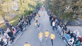 Brummen schoss von den Leuten in den orange Hemden, die Marathon im Stadtpark laufen lassen stock video