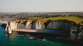 Brummen verschiebt langsam links über schönen weißen Kreideklippen und idyllischer Sonnenuntergangküstenstadt von Etretat Normand stock video footage