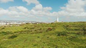 Brummenansicht des weißen Leuchtturmes und der Stadt im Hintergrund Paphos Zypern Gebirgsstadt und Leuchtturm und grünes Gras Luf stock video footage