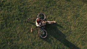 Brummenansicht-Frauenradfahrer, der auf grünem Gras liegt und Handy verwendet stockfoto